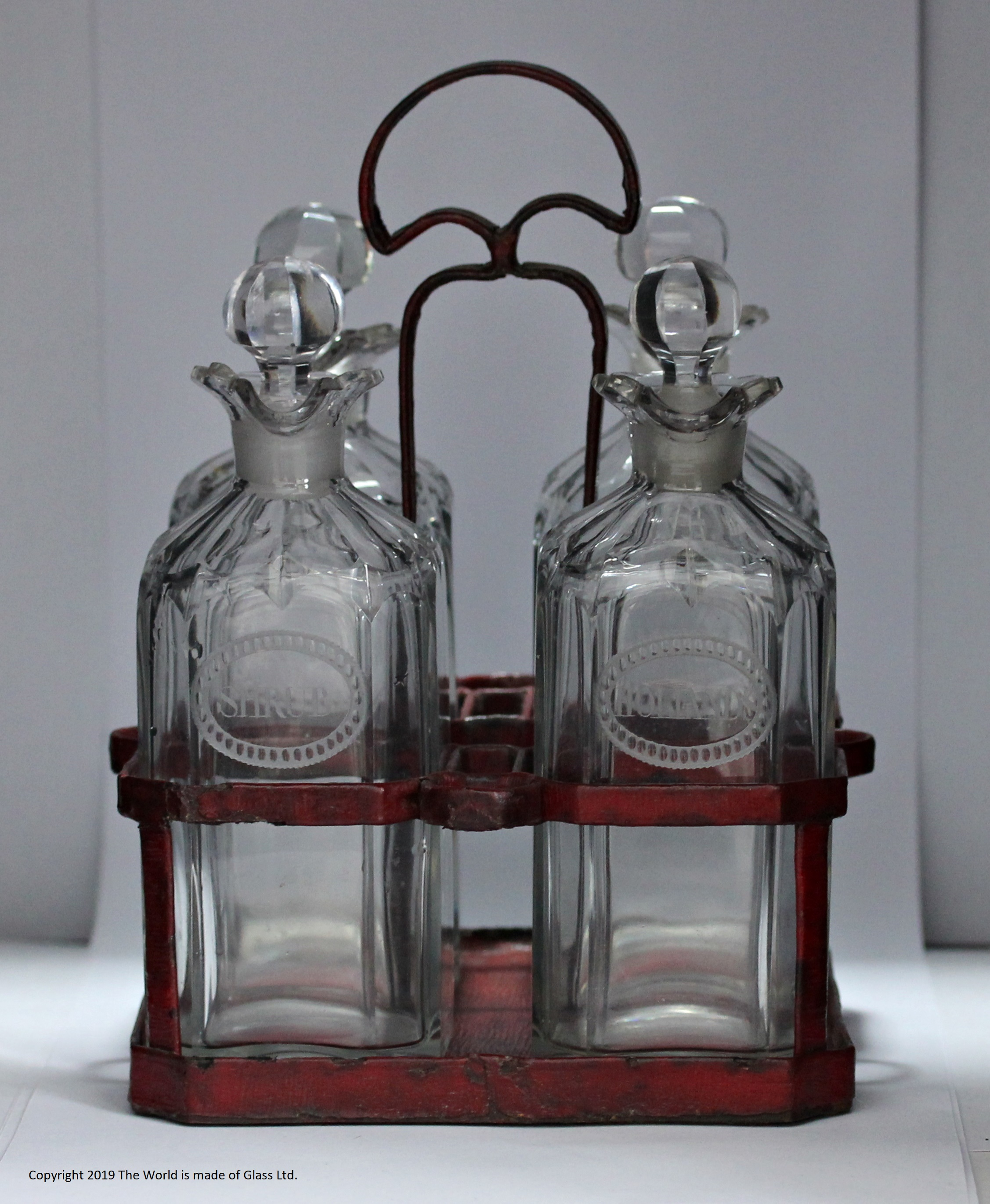 Set of four Georgian engraved case decanters in Moroccan leather covered stand